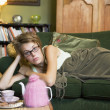 A young woman lying on her couch - Stock Photo
