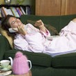 A young woman lying on her couch talking on the phone and eating - Stock Photo