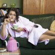 A young woman lying on her couch drinking tea - Stock Photo