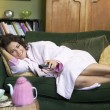 A young woman lying on her couch watching television — Stock Photo #4758424