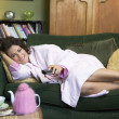 Stock Photo: A young woman lying on her couch watching television