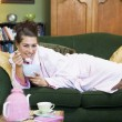A young woman lying on her couch eating cereal — Foto de Stock
