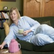 A young woman lying on her couch drinking tea — Stock Photo #4758449
