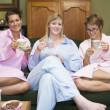 Three young women drinking tea together in their pyjamas — Stock Photo
