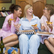 Three young women eating pizza together in their pyjamas — Stock Photo