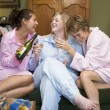 Three young women drinking wine together in their pyjamas — Stock Photo