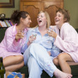 Three young women drinking wine together in their pyjamas — Stock Photo #4758460