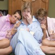 Stock Photo: Three young women crying together in their pyjamas