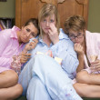 Three young women crying together in their pyjamas — Stock Photo