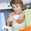 A young woman sitting in a cafe with shopping bags drinking tea — Stock Photo #4758479