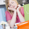 A young woman sitting in a cafe with shoping bags — Stock Photo