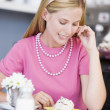 A young woman sitting in a cafe eating a sweet treat - Stock Photo