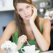 A young woman sitting in a cafe drinking tea — Stock Photo #4758506