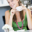 Stock Photo: A young woman sitting in a cafe drinking tea