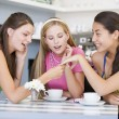 Young women enjoy tea in a cafe - Stock Photo