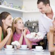 A cafe waiter offers young women teacakes - Stock Photo