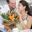 A young man giving flowers to a young woman in a cafe - Stock Photo