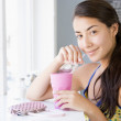 A young woman drinking a milkshake in a cafe - Stockfoto