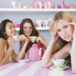Two young women enjoying a tea party while one sits apart — Stock Photo