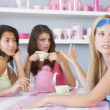 Two young women enjoying a tea party while one sits apart wearin - Stock Photo