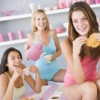 Three young women in their underwear having a tea party - Stock Photo