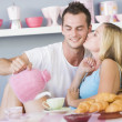 Flirtatious couple enjoying breakfast - 图库照片