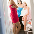 Three young women wearing towels and chatting in the bathroom - Foto de Stock