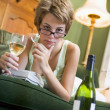 A young woman in her pyjamas drinking wine and smoking — Stock Photo
