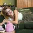 A young woman lying on her couch eating biscuits - Lizenzfreies Foto