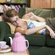 Stock Photo: Young womlying on her couch eating