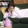 Stock Photo: Young womlying on her couch watching phone