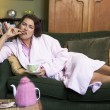 A young woman lying on her couch drinking tea — Stock Photo #4758684