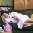 A young woman lying on her couch watching television — Stock Photo