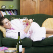 A young woman lying on her couch drinking wine - Stock Photo
