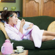 A young woman lying on her couch eating cereal — ストック写真
