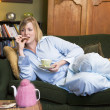 A young woman lying on her couch drinking tea — Stock Photo #4758701