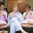 Three young women drinking tea together in their pyjamas - Stockfoto