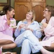 Three young women drinking tea together in their pyjamas - ストック写真
