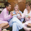 Three young women drinking tea together in their pyjamas - Foto de Stock