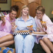 Stock Photo: Three young women eating pizza together in their pyjamas