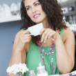 A young woman drinking tea in a cafe - Stock Photo