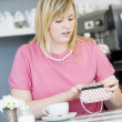 A young woman sitting in a cafe looking worried into her purse — Stock Photo