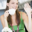 A young woman sitting in a cafe drinking tea and waving — Stock Photo #4758755