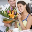 Stock Photo: Young mgiving flowers to young womin cafe