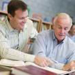 Tutor assisting mature student in library — Stock Photo #4758821