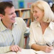 Mature student laughing with tutor in library — Stock Photo