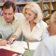 Tutor assisting mature student in library — Stock Photo