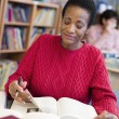 Mature female student studying in library — Stock Photo