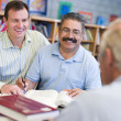 Tutor assisting mature student in library — Stock Photo #4758860