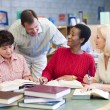 Teacher helping mature students in library — Stock Photo